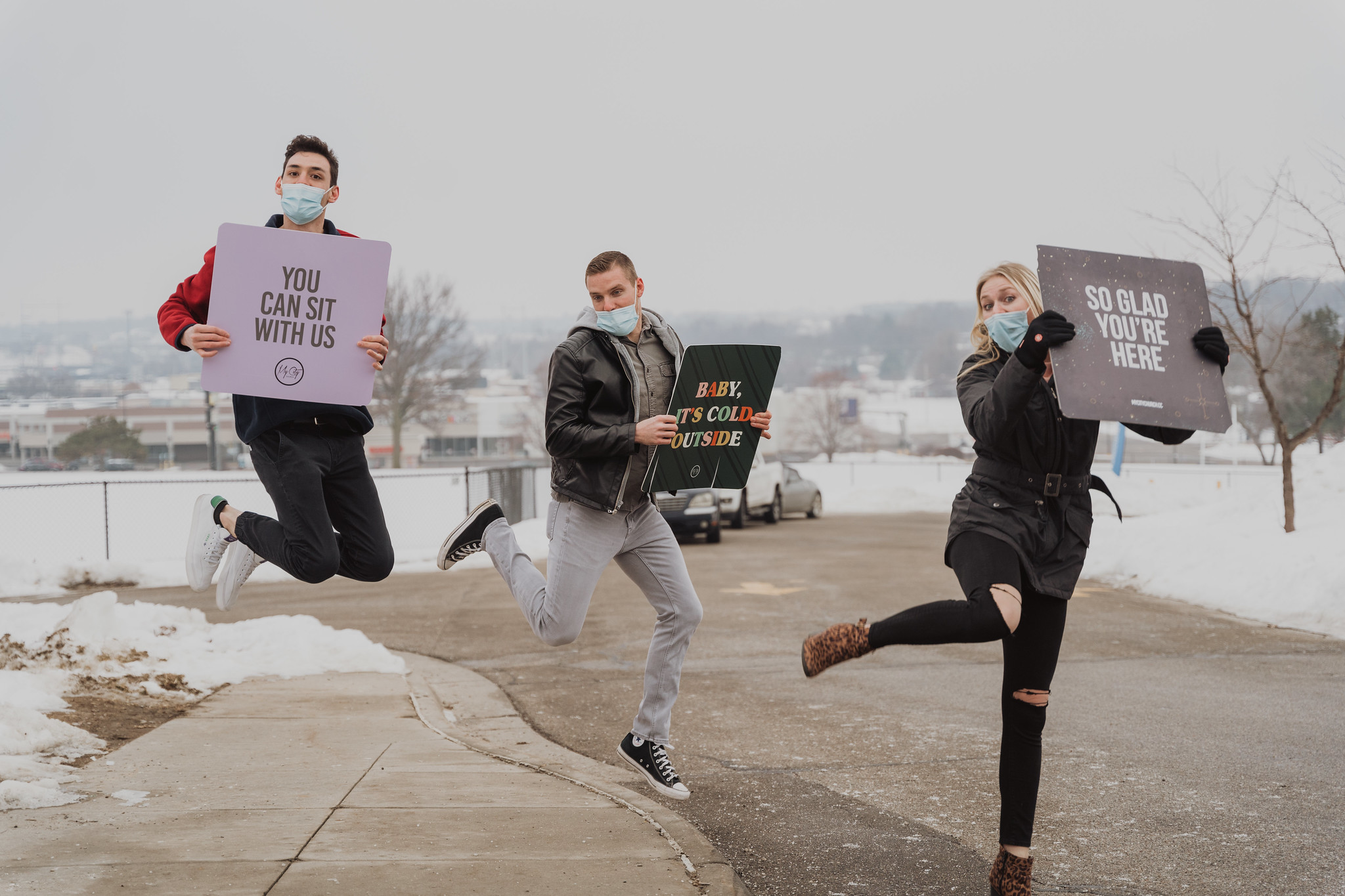 People jumping in the air holding welcome signs in the parking lot at a Christian church in Omaha Nebraska