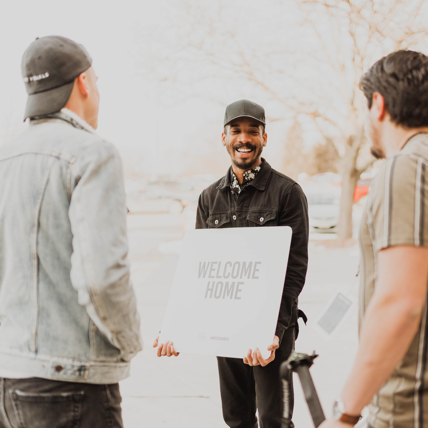 man holding welcome home sign greeting people at an Omaha church