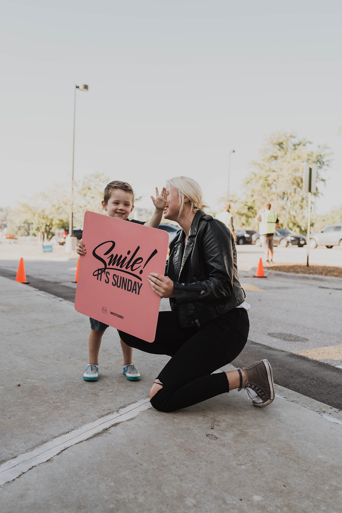 "young woman and a child holding a sign that says, ""smile it's Sunday!"" outside a christian church in omaha nebraska"