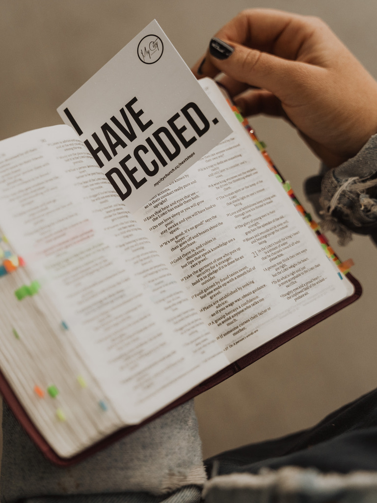 Woman reading the Bible and holding an I Have Decided card at a church in Omaha