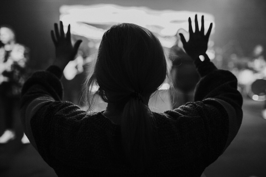 a woman lifting her hands and worshipping Jesus at a christian church service in omaha nebraska