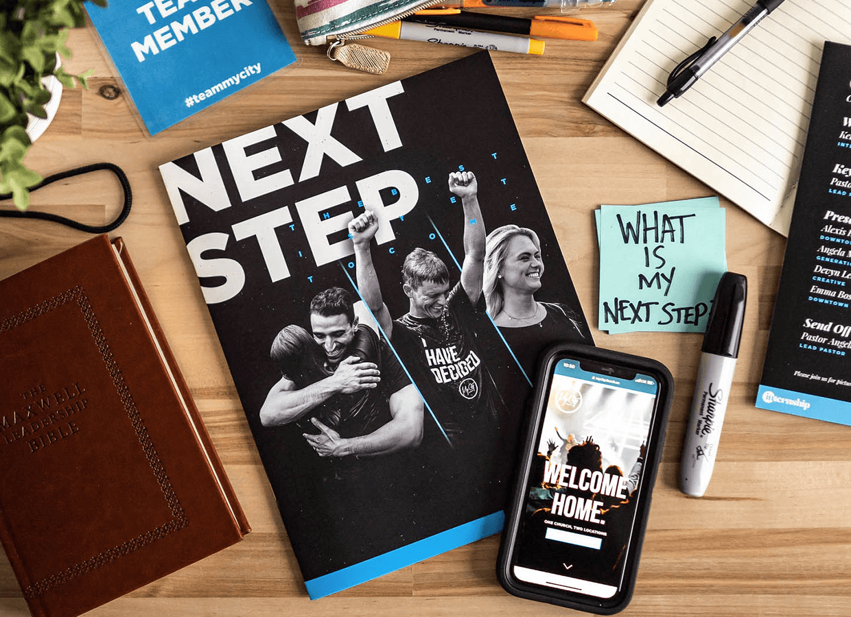 "a desk with a Next Steps booklet and a cell phone sitting on it with a post-it note that says ""what is my next step?"" at a christian church near me"