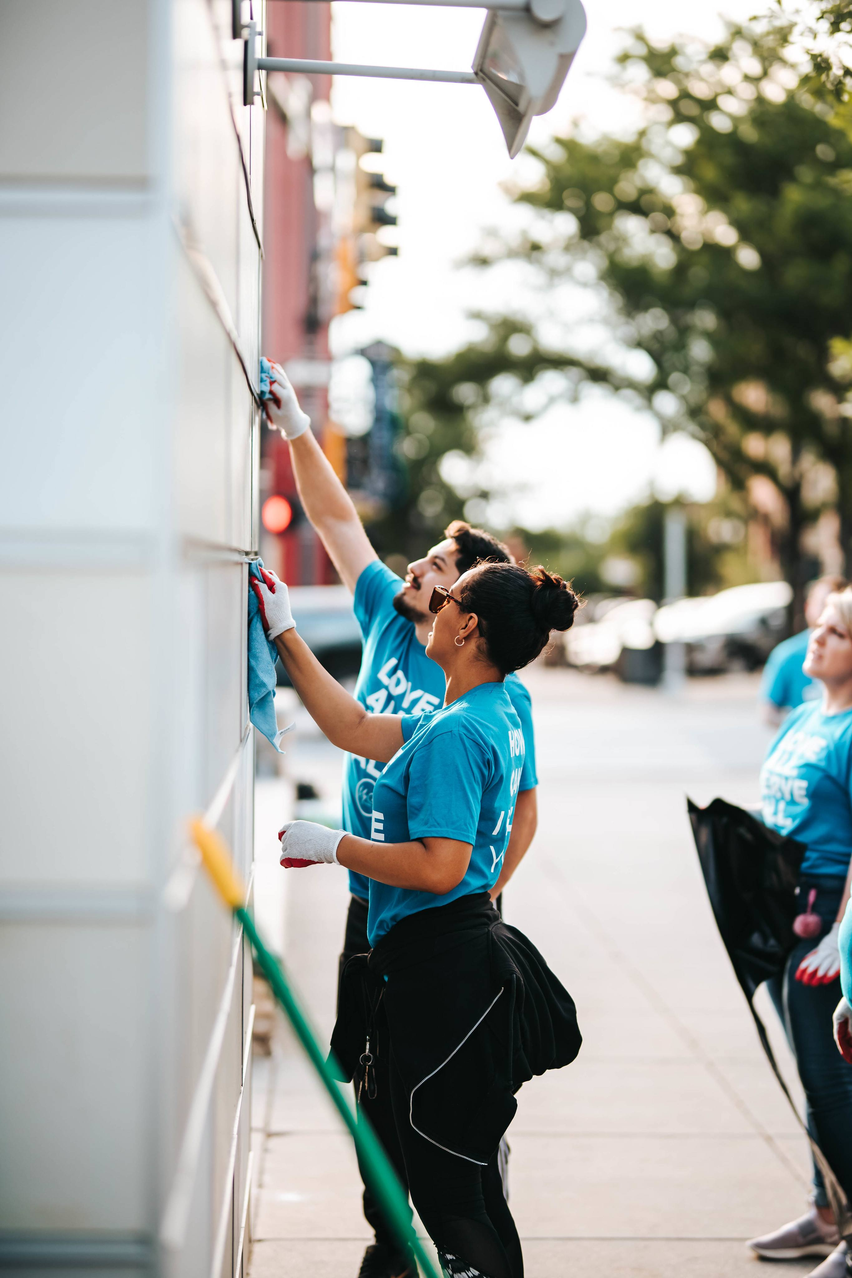 People cleaning graffiti off buildings in Omaha.