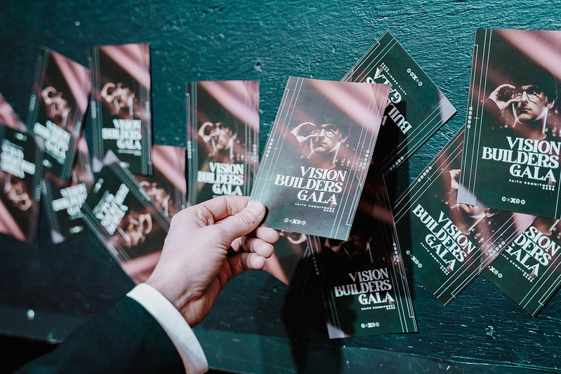 a hand holding an invite card to a Vision Builder's gala in Omaha Nebraska