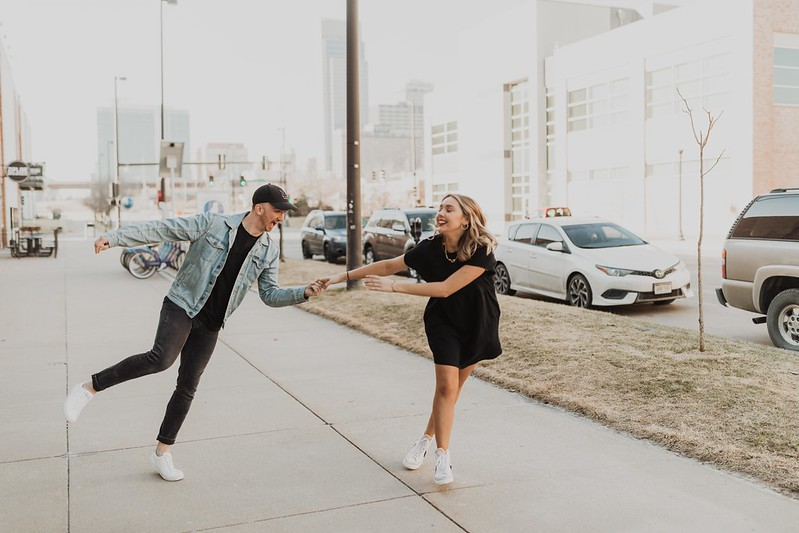a young couple smiling and dancing in Downtown Omaha