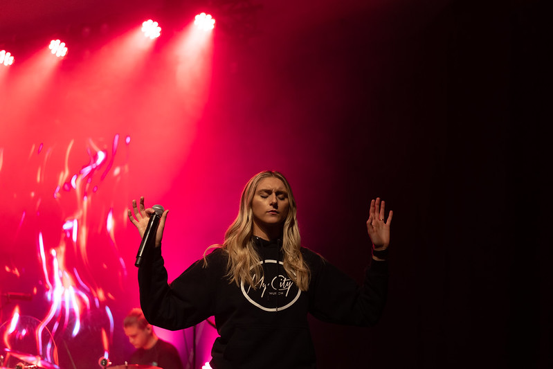 a young woman wearing a black hoodie worshipping God at an Omaha church