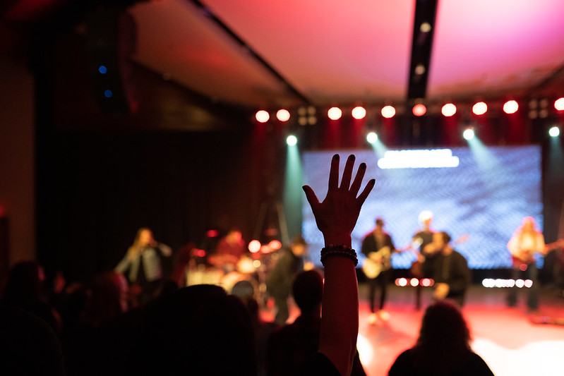 A young woman lifting her hand to worship Jesus