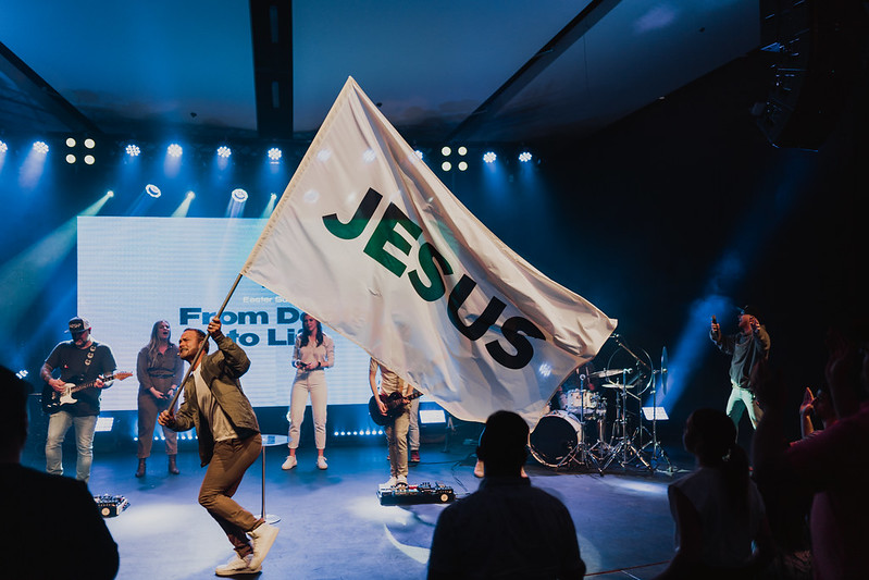 """A pastor running across a stage carrying a flag that says """"Jesus"""" on it while a worship band is singing and playing music at a church in Omaha"""