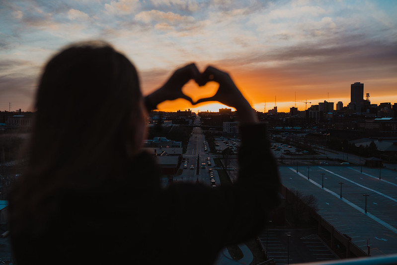 A young woman holding her hands up in the shape of a heart while the sun sets over the city of Omaha