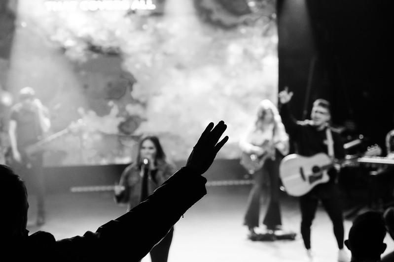 Man worshipping God while a worship band sings to Jesus at a christian church in omaha nebraska