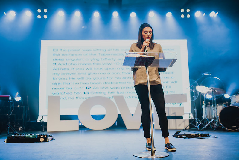 woman pastor preaching on stage at a christian church on Mother's Day in omaha nebraska