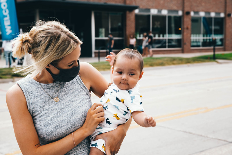 woman holding cute baby outside of christian church