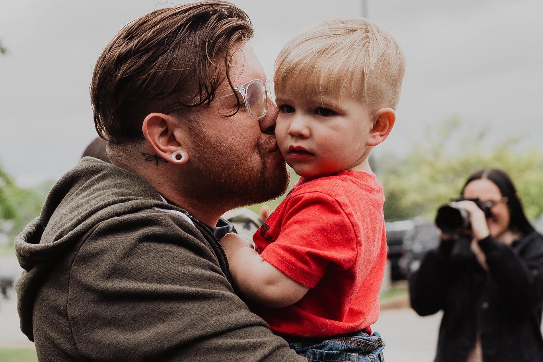 man kissing cute baby outside of church in omaha nebraska