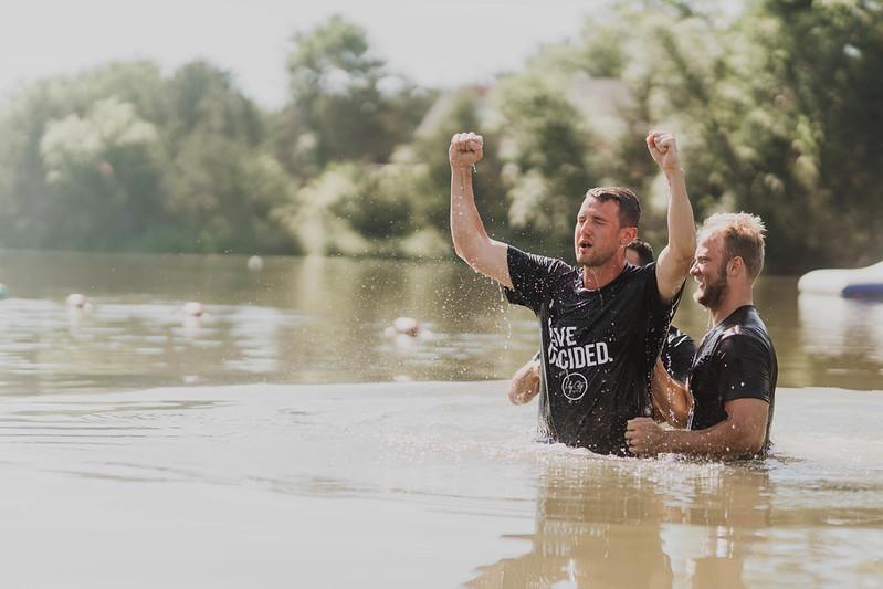 man getting baptized in a lake at camp maranatha in nebraska
