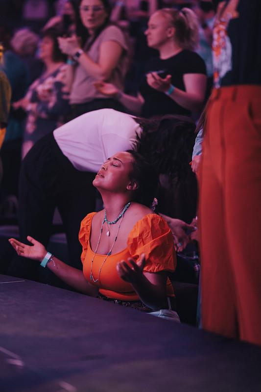 woman worshipping jesus at altar at church in omaha nebraska