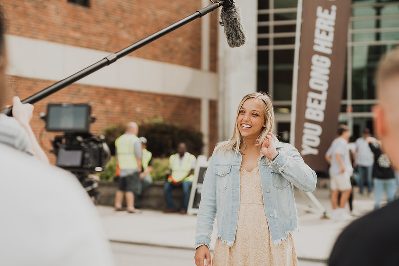 blonde woman smiling and standing outside of christian church in omaha nebraska