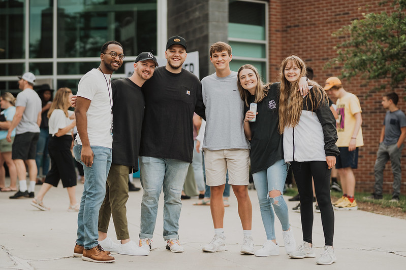 a group of young people looking at the camera smiling outside of a christian church in omaha nebraska
