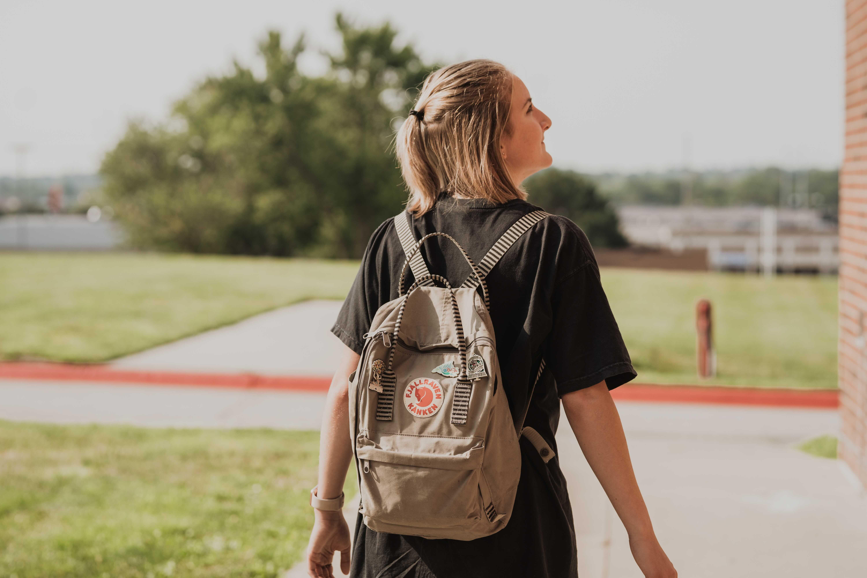 girl walking outside of church in omaha nebraska wearing a backpack