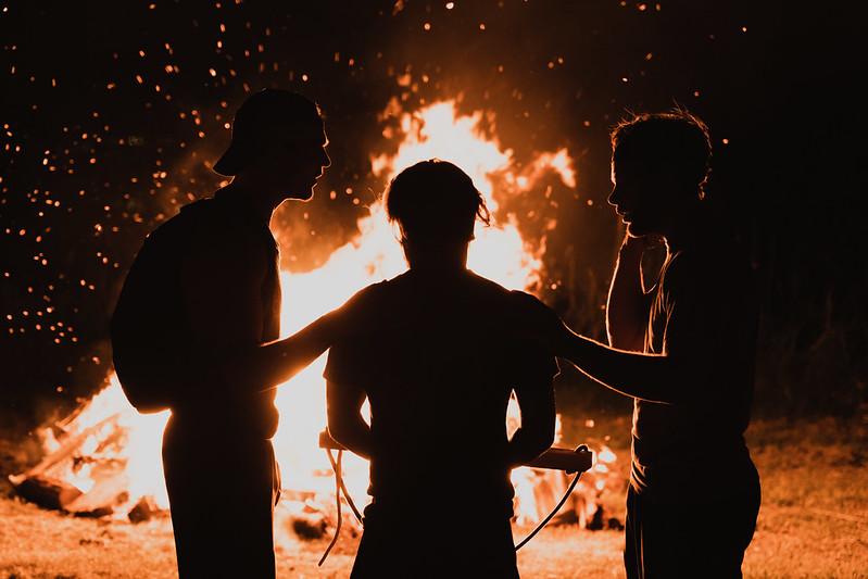 men praying near campfire at bible camp in nebraska