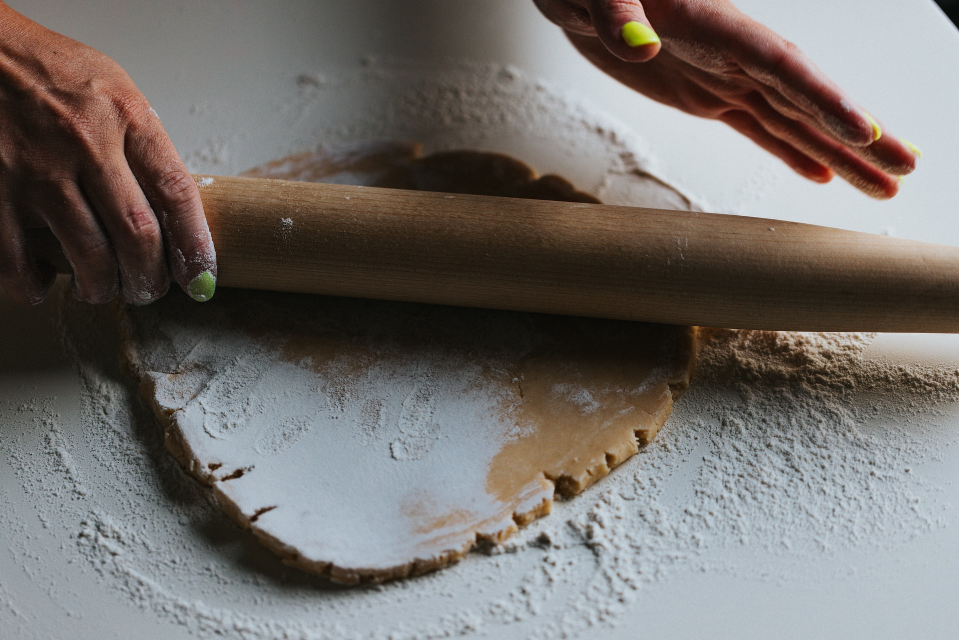 person using a rolling pin to bake