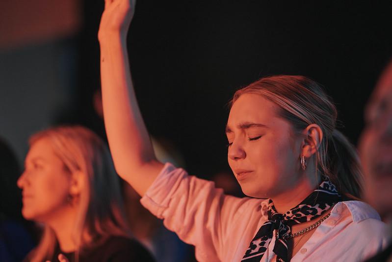 woman raising her hands worshipping jesus at church in omaha nebraska