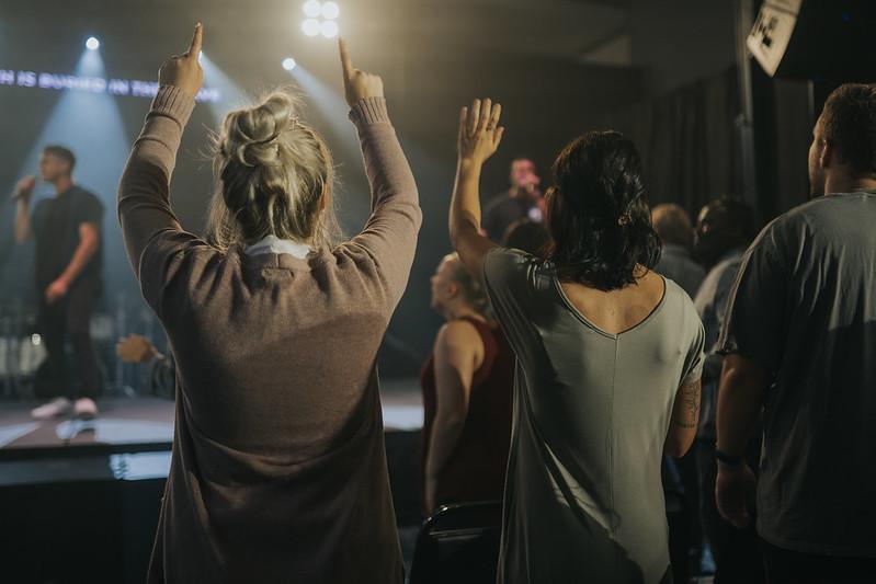 women raising their hands in praise and worship of Jesus christ at church in omaha nebraska