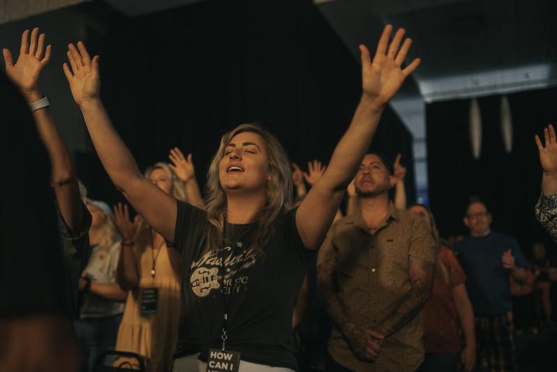 woman raising her hands praising jesus at church in omaha nebraska