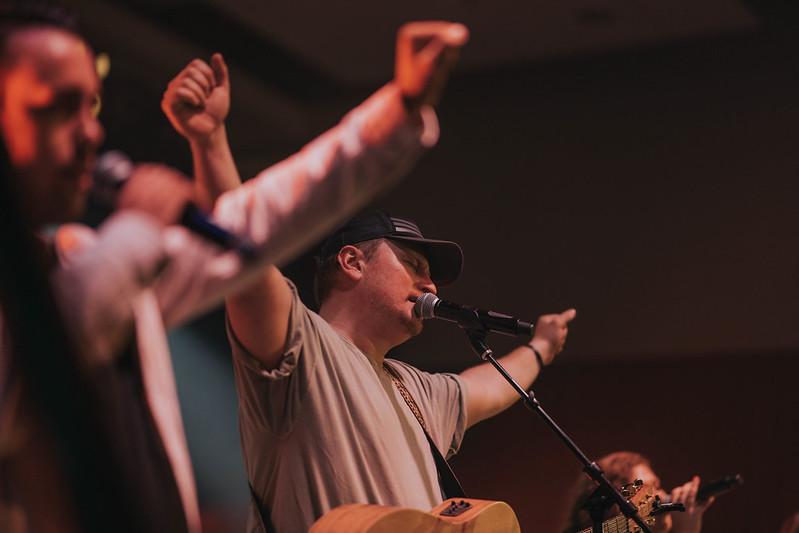 man worshipping jesus on stage at church in omaha nebraska