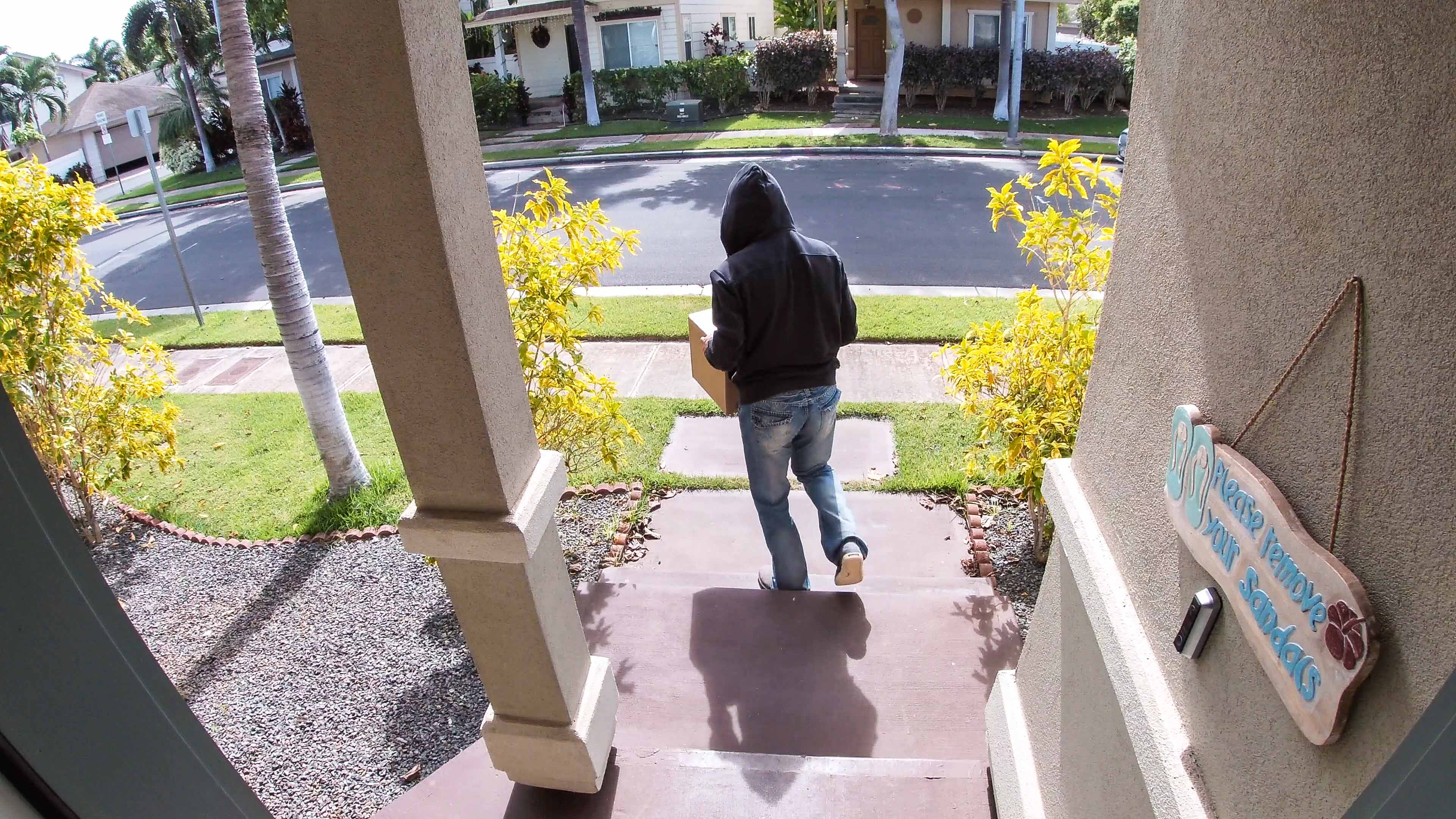 A porch pirate in action, stealing a package from a residential home.