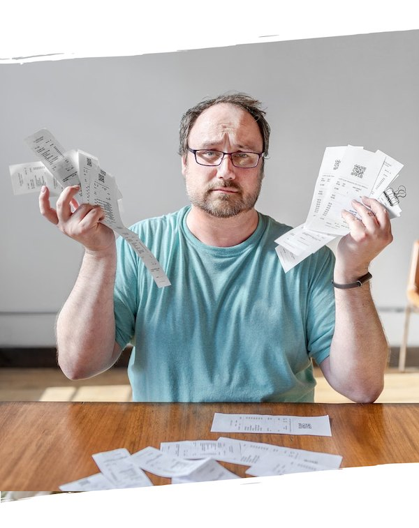 Frustrated business owner surrounded by bills