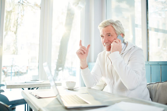 older man wearing white on a business call