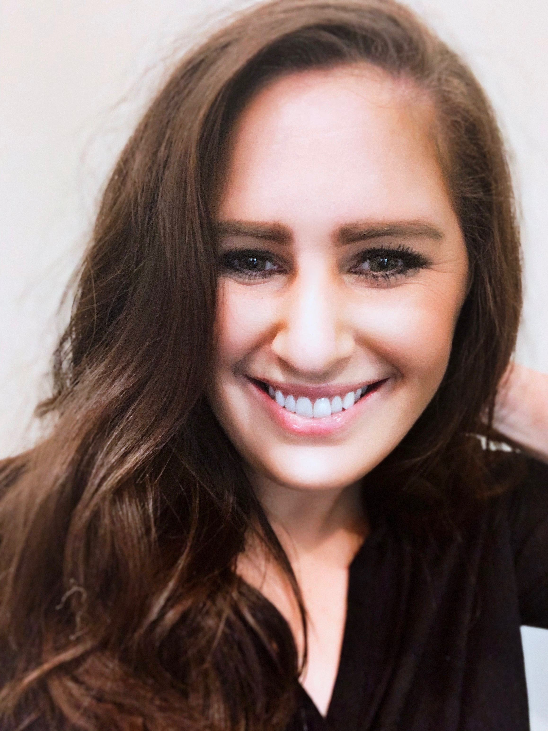 Smiling photo of Gillian Fishman, CEO of Jade. Gillian has brown wavy hair and hazel eyes, and is wearing a black v-neck shirt.