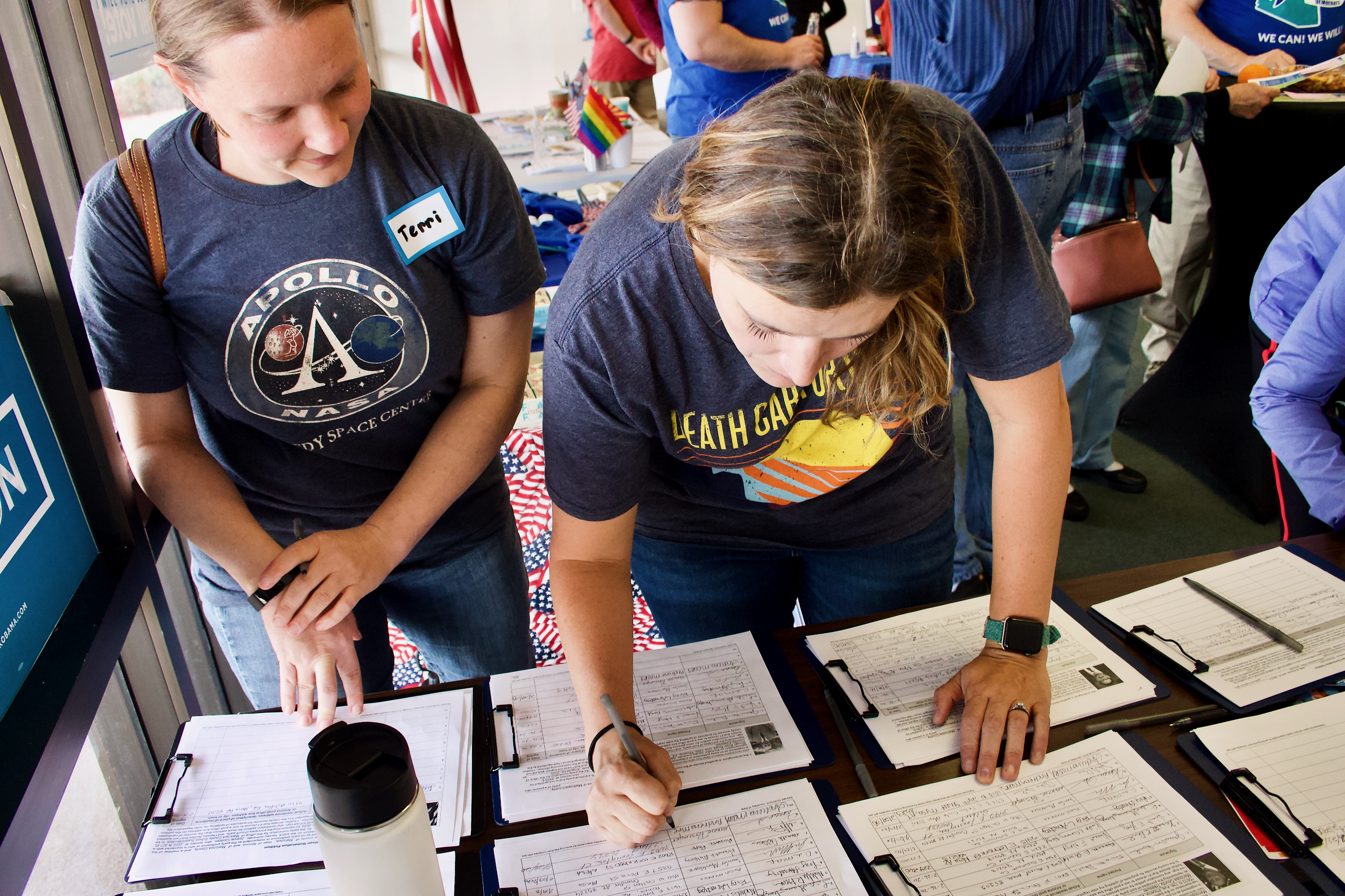 Two women signing petitions.