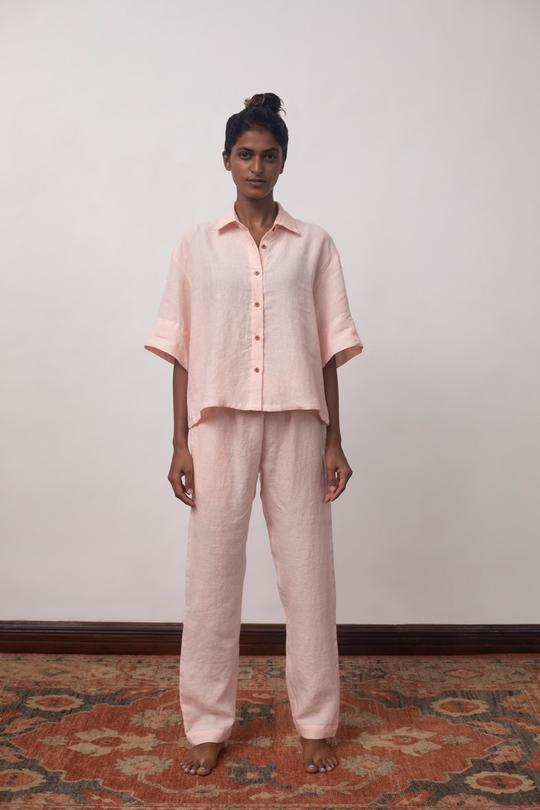 This pure linen shirt and pyjama set is so comfortable, it will sing you to sleep. Wear at night, but also while lounging through the day, G&T in hand, or while working from home. This versatile, easy-to-maintain set is created in shades of Cinnamon and Gulabjal (blush pink), with details that appear slowly like little surprises - wooden buttons, drawstrings, pockets, best wishes. Note: Please wash separately before use, dark colours run during the first wash or two. 100% linen, European flax — a natural fibre. Linen is biodegradable, and therefore a sustainable, eco-friendly choice. Great for your skin — anti-static with its own pH balance. All season natural insulator - cool in summer, warm in winter. Repels micro-organisms and absorbs moisture. Ages gracefully, becoming softer with every wash. Consciously crafted — low-impact dyeing, no harsh chemical treatments. Designed and made in India. Product colour may vary slightly due to photographic and natural light sources.