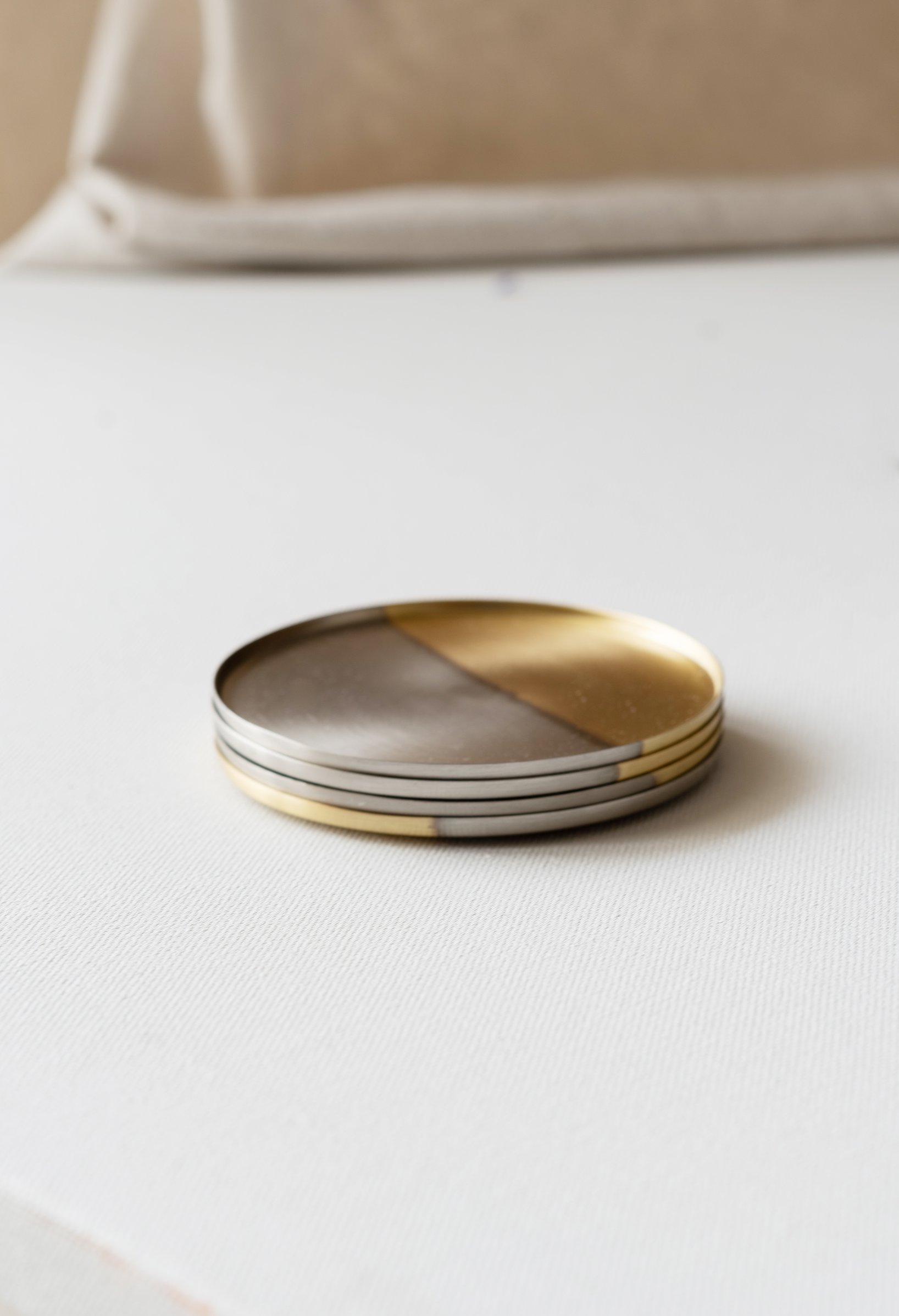 A set of 4 clean and minimal two-tone coasters to add a hint of luxury to your everyday life. These elegant brass coasters are made from a single sheet of brass in our foundry using pure metals and alloys that will oxidise over time. Each one is backed with natural cork to protect your delicate surfaces.
