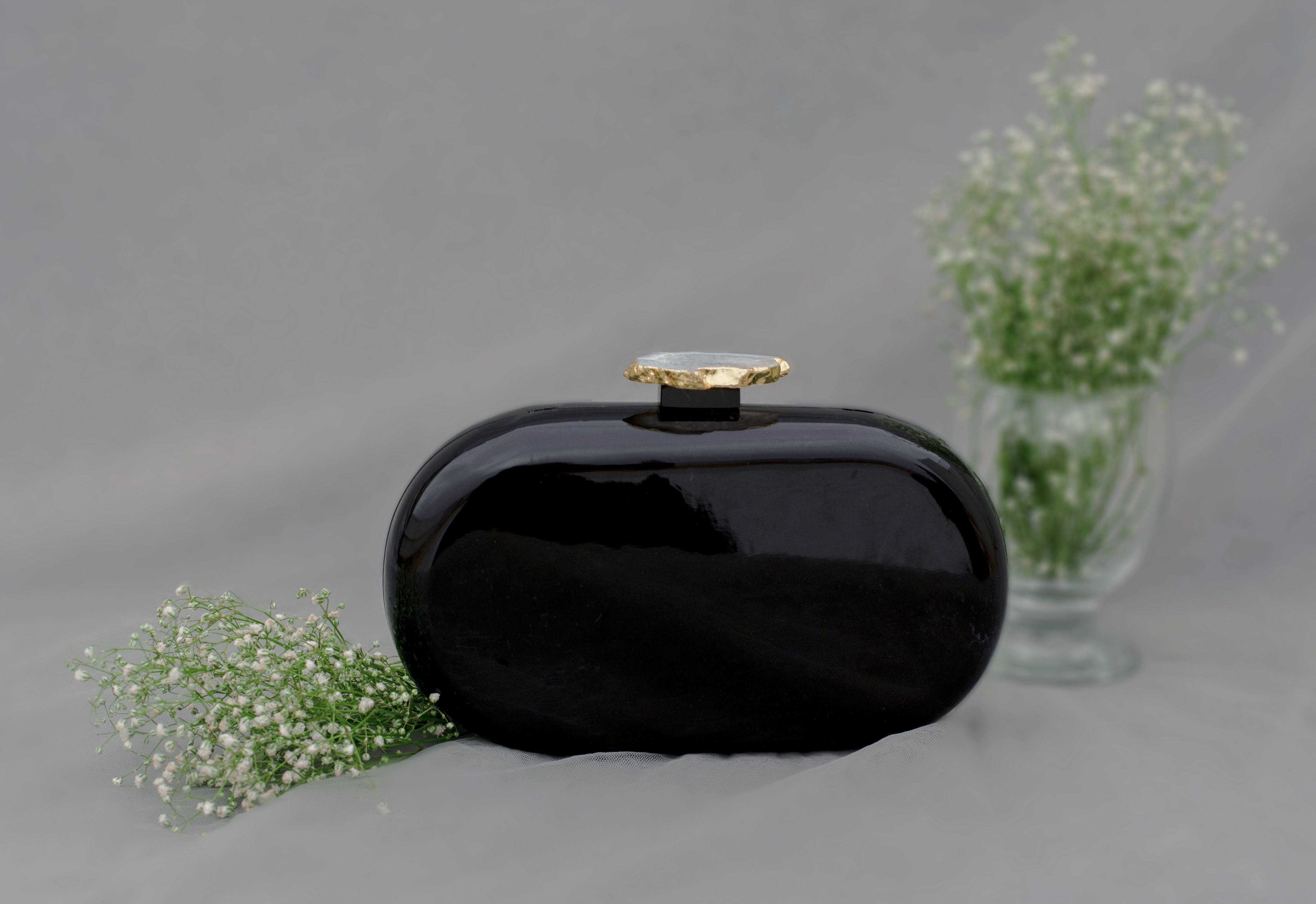 """""""Classic and Timeless designs that you can cherish forever! This Clutch is made of Black Corian Marble - an heirloom piece that you can pass it on from generation to generation to keep the bond alive. Express yourself with this edgy Corian Clutch, handcrafted with agate stones that are irreplaceable for its natural shape and texture. It can be a perfect evening accessory to style your festive as well as your party looks and comes with a golden Sling. The Agate stone can vary in shape and color as it is a natural stone."""""""