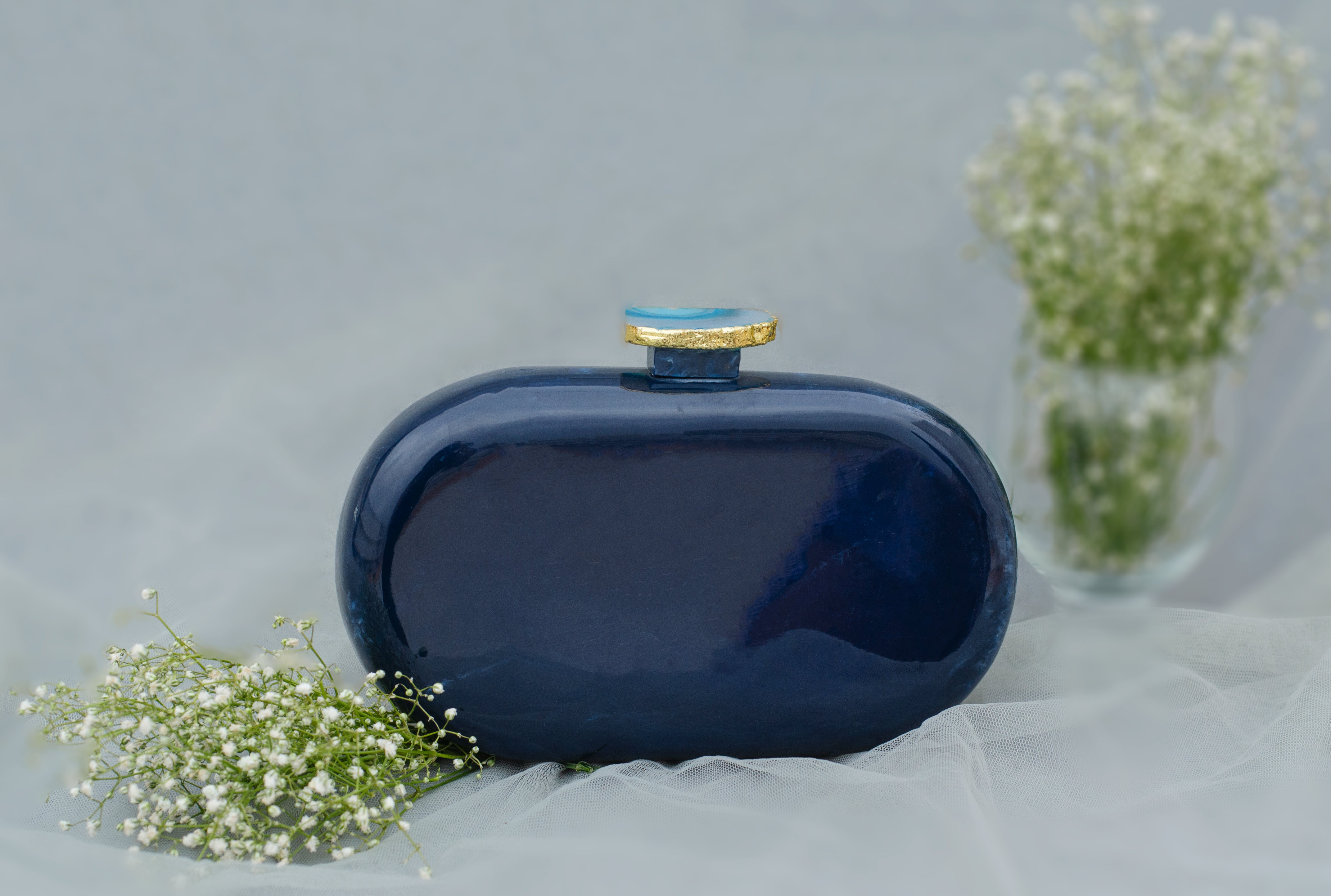 """""""Classic and Timeless designs that you can cherish forever! This Clutch is made of Blue Corian Marble - an heirloom piece that you can pass it on from generation to generation to keep the bond alive. Express yourself with this edgy Corian Clutch, handcrafted with agate stones that are irreplaceable for its natural shape and texture. It can be a perfect evening accessory to style your festive as well as your party looks and comes with a golden Sling. The Agate stone can vary in shape and color as it is a natural stone."""""""
