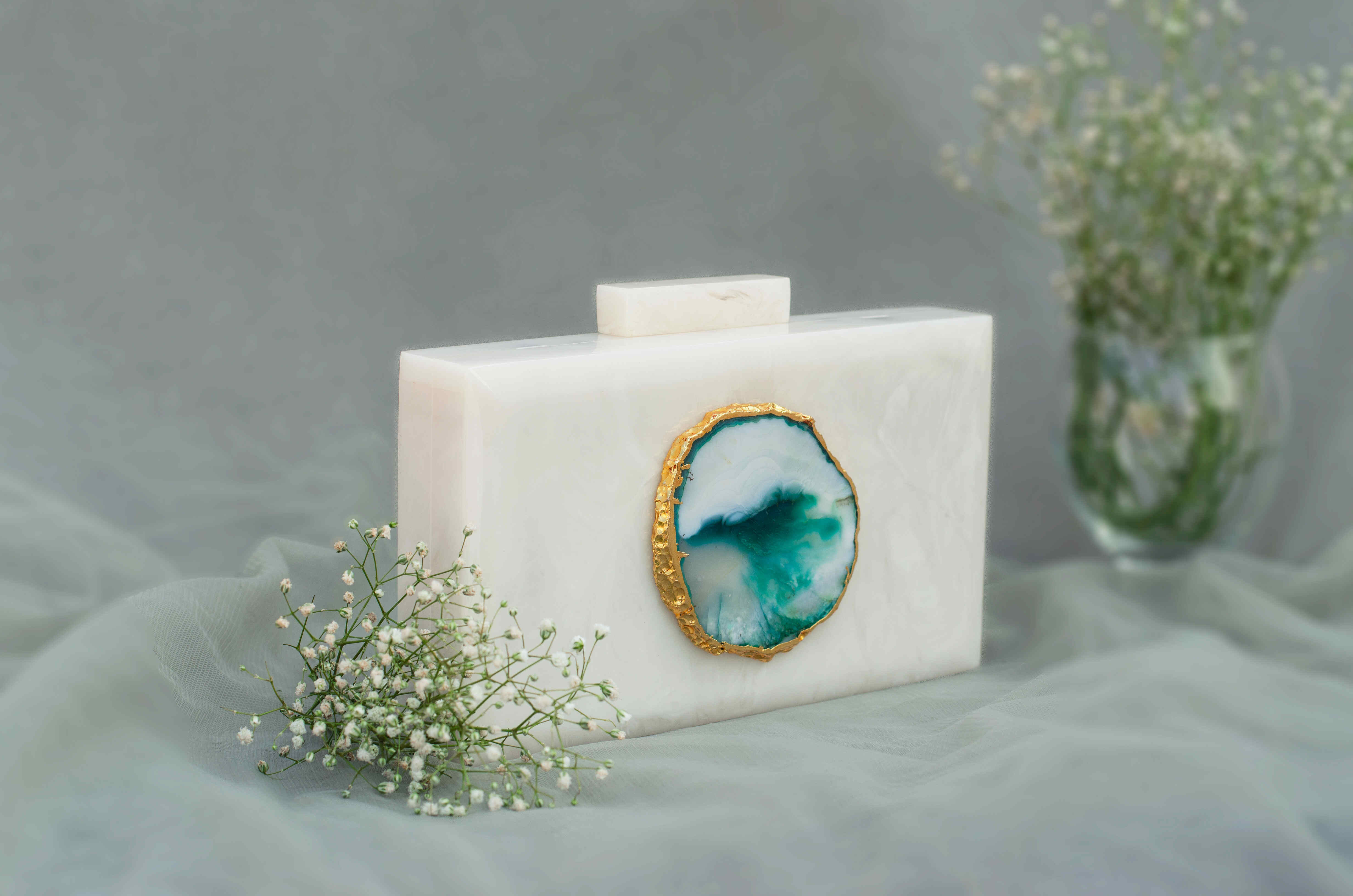 """""""Classic and Timeless designs that you can cherish forever! This Clutch is made of White Corian Marble - an heirloom piece that you can pass it on from generation to generation to keep the bond alive. Express yourself with this edgy Corian Clutch, handcrafted with agate stones that are irreplaceable for its natural shape and texture. It can be a perfect evening accessory to style your festive as well as your party looks and comes with a golden Sling. The Agate stone can vary in shape and color as it is a natural stone."""""""