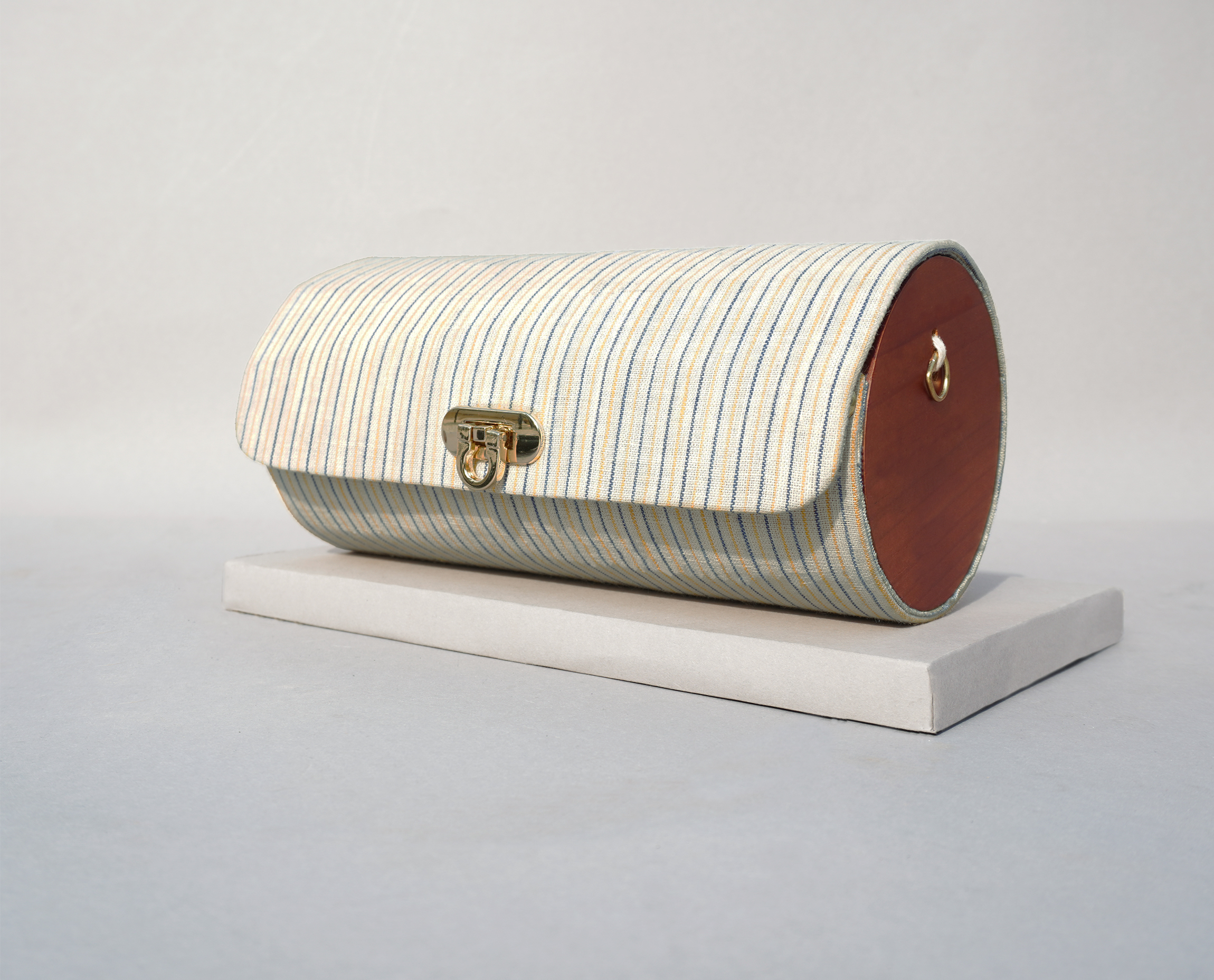 This Cylindrical Khadi Bag is a slow fashion handcrafted accessory for your everyday carry. It is made of hand-spun/hand-woven organic cotton and finished with wood and elegant hardware that compliments your casual as well as fusion wear. It comes with two detachable belts - a cotton strap made from the same fabric and a metal chain to style it as a Shoulder or a Cross Body Accessory. You can also give it for an easy wash (Dry clean only).