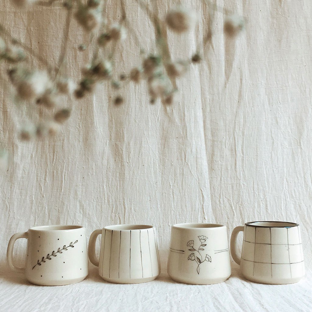 """An assortment of four distinct patterns, bougainvillea and durba flower teacups paired with stripe and check cups. Perfect companion for friends and family coming together and sharing evening chai. Product Description : Color - Ivory Dimension - 2.75"""" X 2.5"""" Weight - 200 gms (each) Capacity - 200 ml (each) Material - Stoneware Wash & Care - Foodsafe, Microwave & Dishwasher safe"""