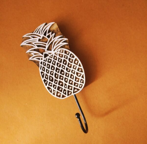 """""""Our Pina wall hook is hand-carved onto indigenous rosewood varieties and fixed with a wrought iron hook to give the wall hook a charming look & feel while making it a utility piece that'll add to your decor. Size: 15cm long pineapple, 4-5cm long hook culed inwards (approx)"""""""