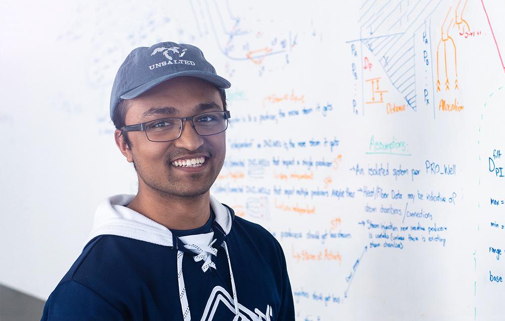 Shounak animatedly describing a problem on a whiteboard