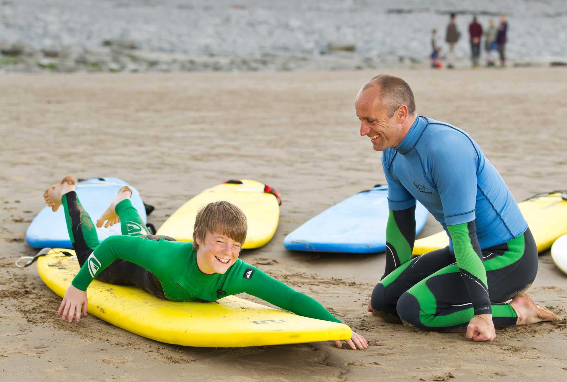 Surfing instructor teaching a boy how to surf