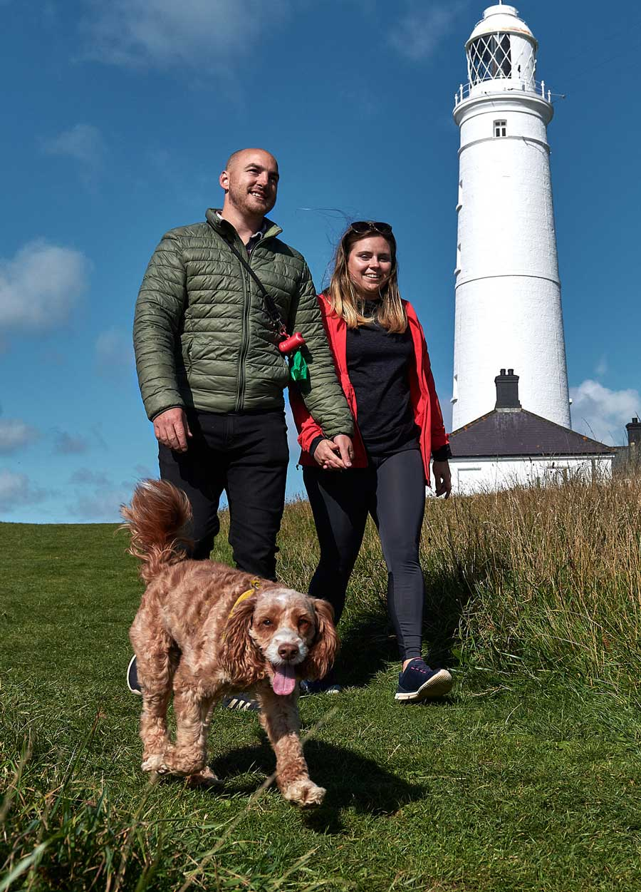 A couple walking their pet dog in front on Nash point lighthouse