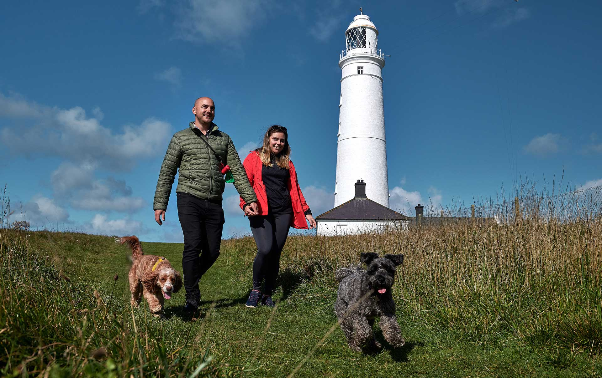Couple walking in front of Nash Point lighthouse with two dogs