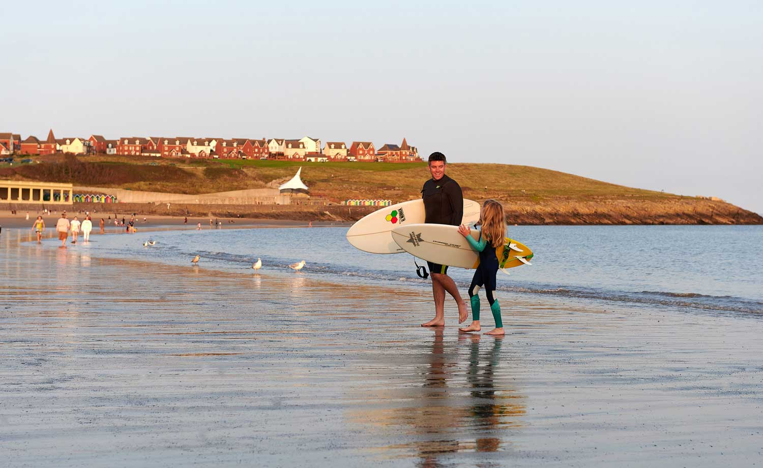 A father and daughter carrying surfboards with Barry beach huts in the distant background