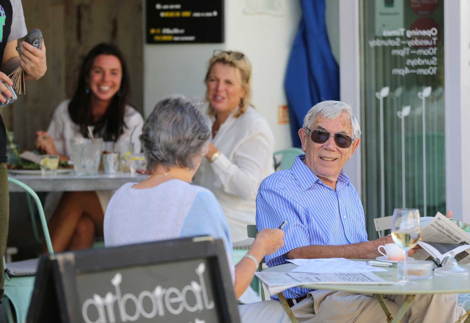 A couple enjoy wine in the sun at a cafe