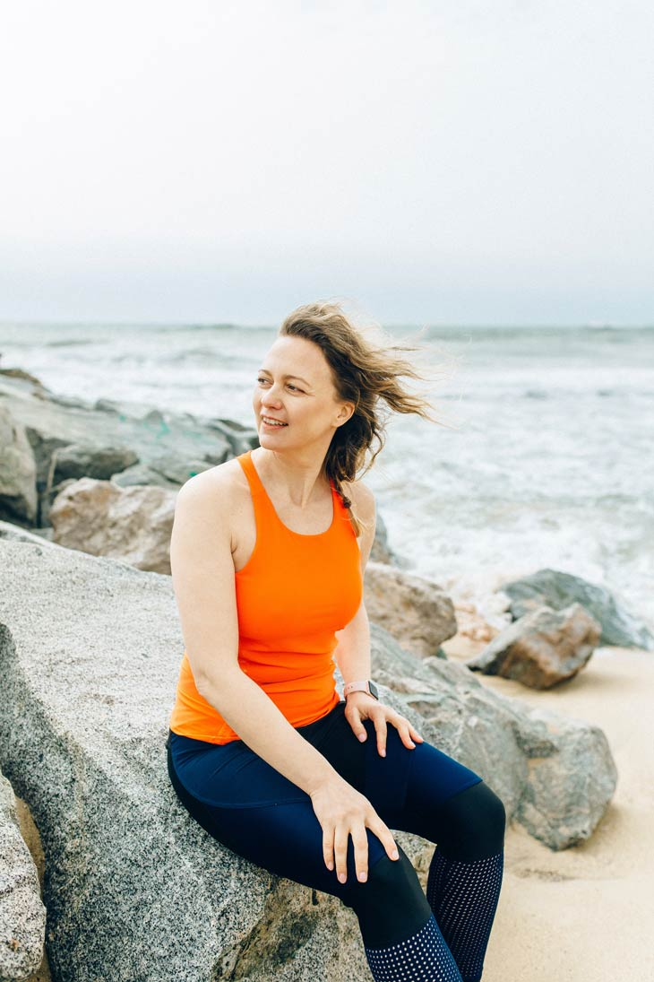 Woman looks optimistically away from camera while resting on the rocks of a beach after exercising.