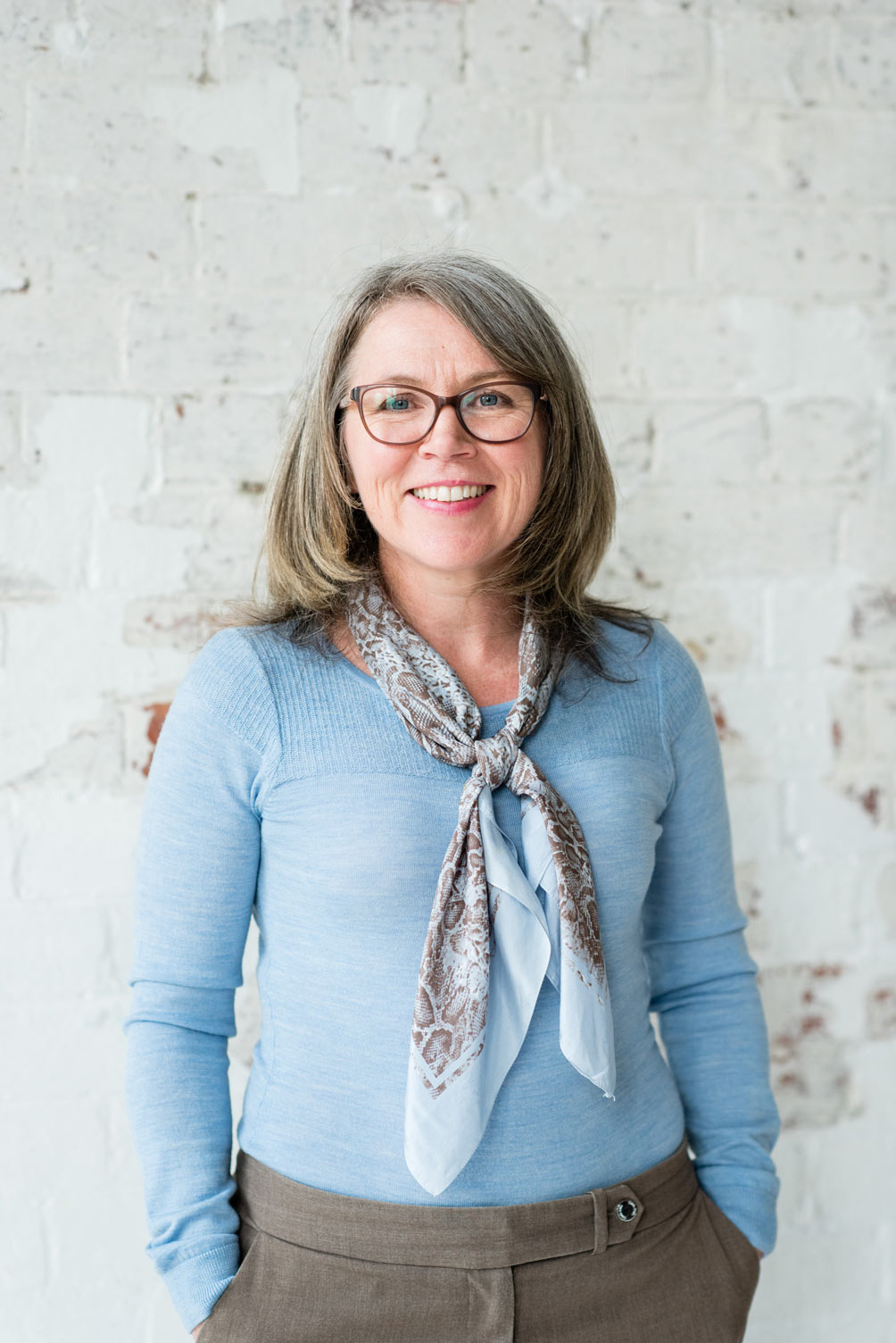 A portrait shot of Rebecca Hughes standing and smiling at the camera.