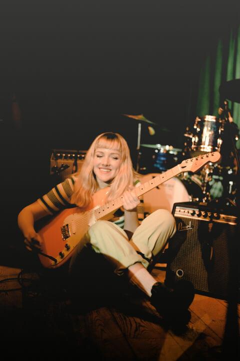 artist on set preparing her guitar